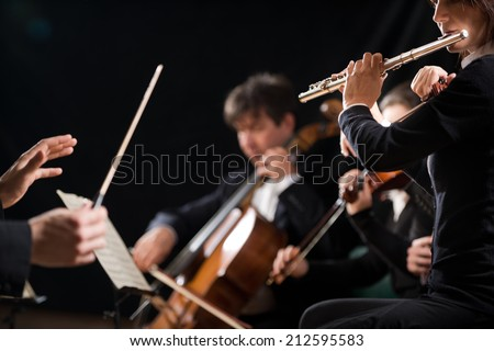 Conductor directing symphony orchestra in concert with flutist on foreground. - stock photo