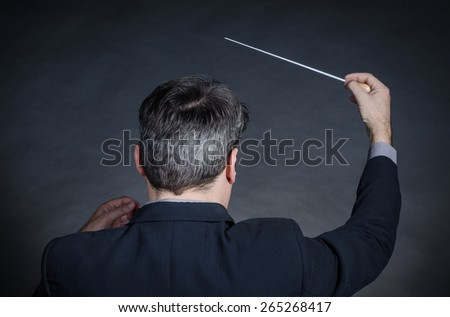 Conductor with back to camera gesturing with baton - stock photo