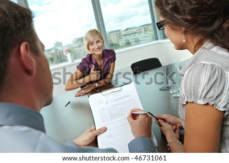 Conductors holding questionnaire form during the job interview, applicant's reults are excellent. Focus placed on sheet in front. - stock photo