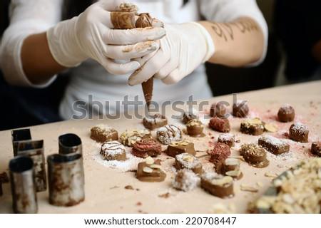 Confectioner decorated chocolate. - stock photo