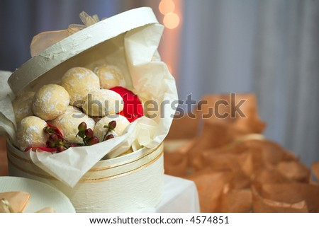 Confectionery and cookies in white gift boxes with ribbons as wedding guest gifts and table decorations - stock photo