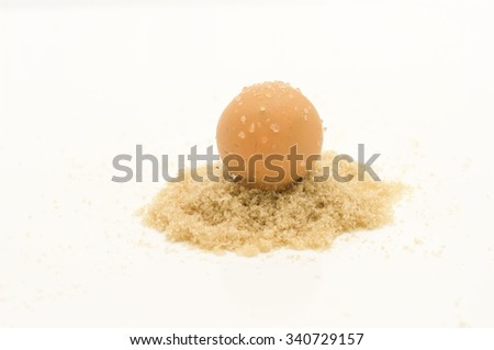 Confectionery of orange flavor. The candy ball coated with sugar on heap of brown sugar is isolated on white background. - stock photo