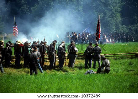 Confederates volley fire on advancing Union soldiers,Civil War battle reenactment - stock photo