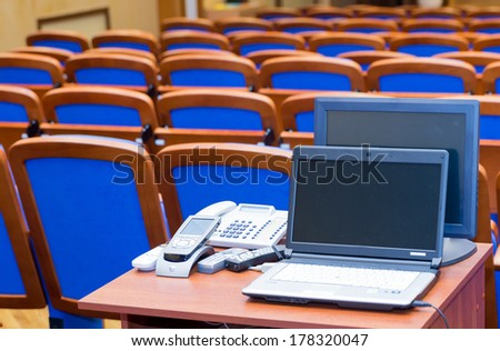 Conference hall with rows of blue seats and rostrum - stock photo