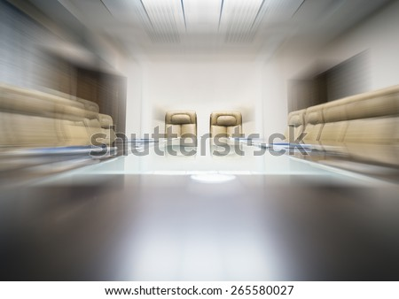 conference room with wooden table and beige leather armchairs, motion blur - stock photo