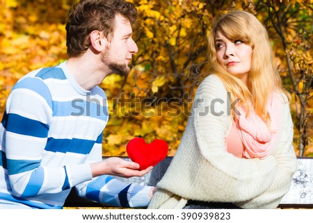 Confessing love and affection with romantic gesture. Rejection and disapproval. Negative reaction. Pair sit on bench in park man hold plush heart showing his emotions girl refuse. - stock photo