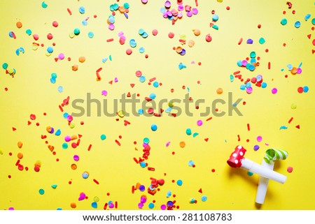 confetti on yellow background - stock photo