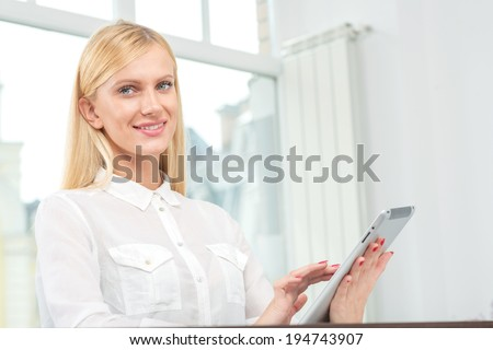 Confidence in business. Cheerful businesswoman working on the tablet. Charming blond girl sitting in the office. - stock photo