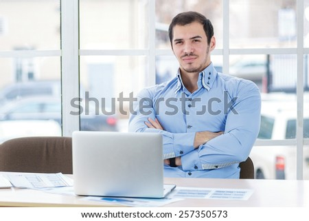 Confidence in the business. A successful and confident businessman working at his laptop and crossed his arms while handsome young man sitting in the office at the table. - stock photo