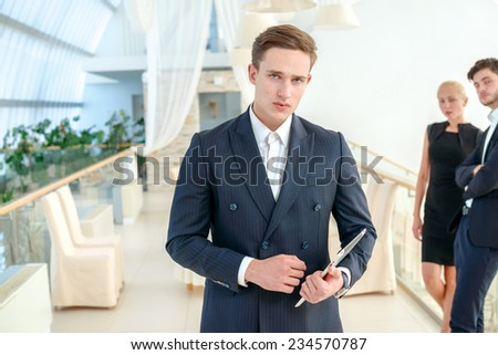Confidence in the power business. Confident businessman holding a tablet and strictly looking at the camera while his colleague businessmen standing and talking in the background - stock photo