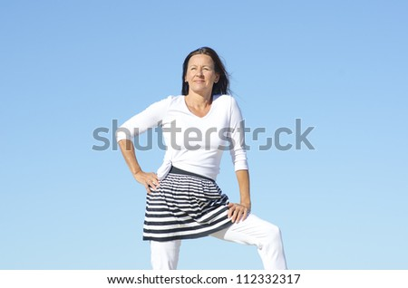 Confident and attractive mature woman looking fit, sporty and healthy, posing outdoor isolated with blue sky as background and copy space. - stock photo