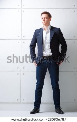 Confident and charisma. Full length portrait of young man looking away holding hands in pockets while standing against white wall. - stock photo