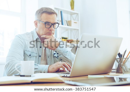 Confident and concentrated. Thoughtful mature man looking at his laptop and keeping hand on chin while sitting at his working place - stock photo