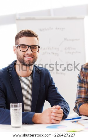 Confident and creative. Confident young man in smart casual wear looking at camera and smiling while sitting at his working place with whiteboard in the background - stock photo