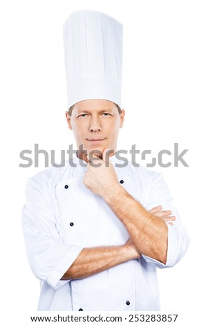 Confident and experienced chef. Confident mature chef in white uniform holding hand on chin and looking at camera while standing against white background - stock photo