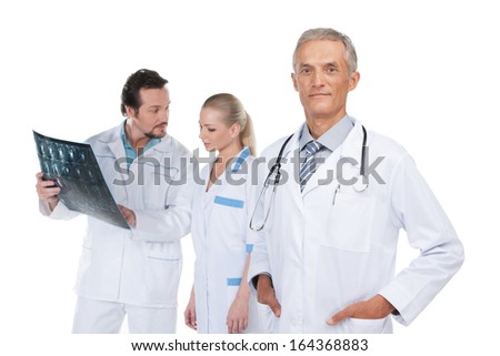 Confident and experienced Head physician on foreground. Couple of doctors discussing X-ray on background  - stock photo
