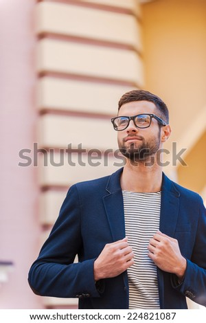 Confident and handsome. Handsome young man in eyeglasses adjusting his jacket and looking away while standing outdoors - stock photo