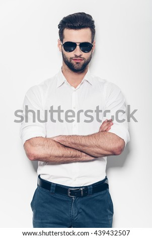 Confident and handsome. Handsome young man in white shirt keeping arms crossed and looking at camera while standing against white background  - stock photo