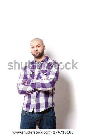 Confident and handsome. Portrait of young latin man in casual shirt keeping arms crossed and looking at camera while standing against white background. - stock photo