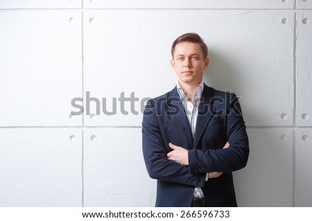 Confident and handsome. Portrait of  young man in jacket keeping arms crossed and looking at camera while standing against white wall. - stock photo