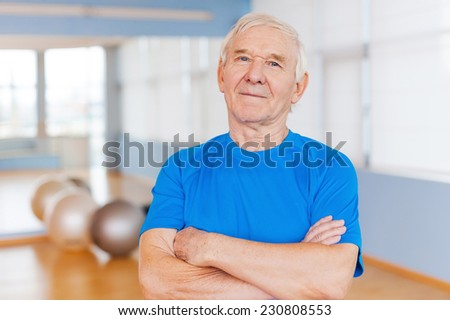 Confident and healthy. Confident senior man keeping arms crossed and looking at camera while standing in health club with sports equipment laying in the background - stock photo