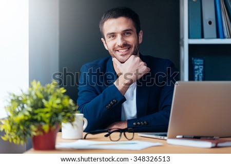 Confident and inspired. Confident young man holding hand on chin and smiling while sitting at his working place in office - stock photo