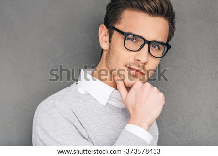 Confident and intelligent. Confident young man in glasses holding hand on chin and looking at camera while standing against grey background - stock photo