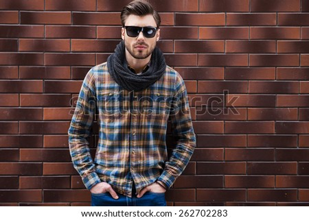 Confident and stylish. Handsome young man leaning the brick wall and holding hands in pockets while standing against brick wall - stock photo