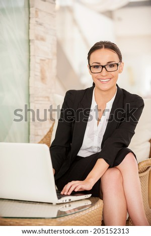 Confident and successful business lady. Confident young woman in formalwear working on laptop and smiling while sitting at the comfortable chair - stock photo