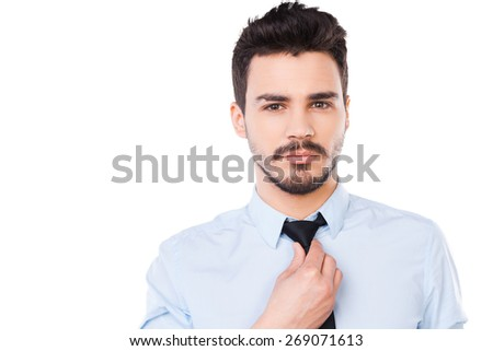 Confident and successful. Confident young man in shirt and tie looking at camera and adjusting his necktie while standing against white background - stock photo