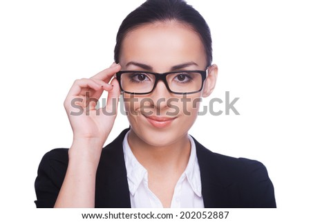 Confident and successful. Confident young woman in formalwear adjusting her eyeglasses and looking at camera while standing isolated on white - stock photo