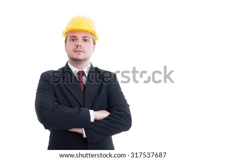 Confident and successful contractor, foreman, or architect with arms crossed wearing a yellow hardhat - stock photo