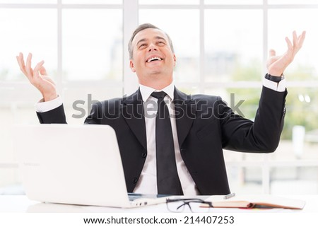 Confident and successful. Happy mature man in formalwear smiling and gesturing while sitting at his working place - stock photo