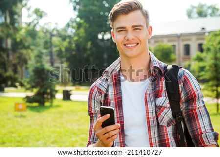 Confident and successful student. Handsome male student holding mobile phone and smiling while standing outdoors - stock photo