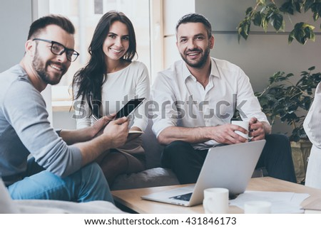 Confident and successful. Three confident business people in smart casual wear looking at camera and smiling while sitting together at the desk in office  - stock photo