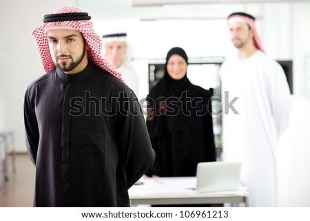 Confident arabic young business executive with his team in the background - stock photo