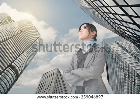 Confident Asian business woman stand and think, closeup portrait with office building background. - stock photo