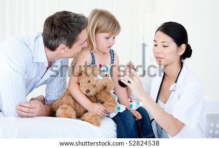 Confident asian female doctor giving syrup to a little girl against white background - stock photo