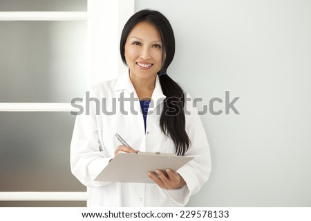 Confident Asian woman doctor taking notes on a clipboard when visiting a patient. This photo has been produced with professionals. - stock photo