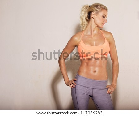 Confident athletic woman with sixpack abs posing - stock photo
