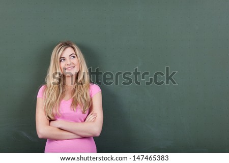Confident attractive young blond schoolgirl with a bright idea standing with her arms folded in front of a blank chalkboard smiling and looking up, with copyspace - stock photo