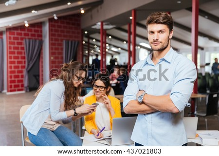 Confident attractive young businessman standing with arms crossed with his colleagues on background - stock photo