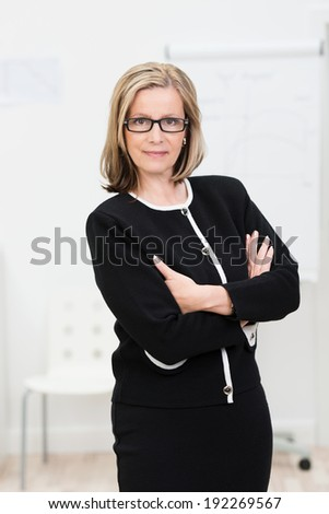 Confident austere middle-aged businesswoman wearing glasses standing with her arms folded looking intently at the camera - stock photo