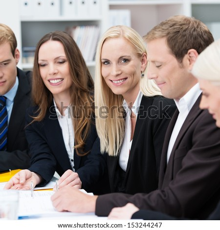 Confident beautiful female team leader sitting in a business meeting at a table with a group of her colleagues turning to smile at the camera, selective focus - stock photo