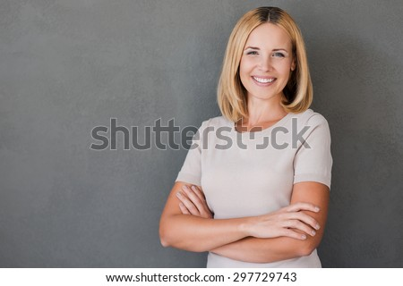 Confident beauty. Cheerful mature woman keeping arms crossed and smiling while standing against grey background - stock photo
