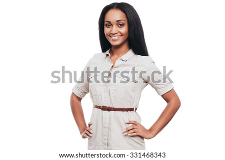 Confident beauty. Smiling young African woman holding hands on hips and looking at camera while standing against white background - stock photo
