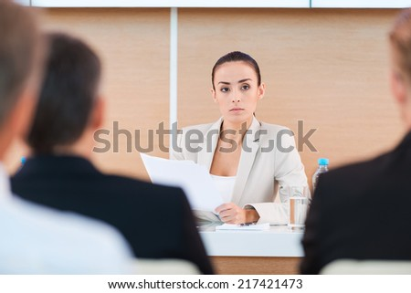 Confident business expert. Confident mature man in formalwear sitting at the table with large monitor upon his head and with people on foreground  - stock photo