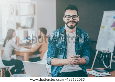 Confident business expert. Confident young man holding smart phone and looking at camera with smile while his colleagues working in the background - stock photo