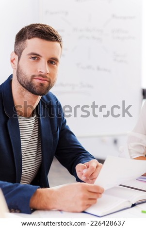 Confident business expert. Confident young man in smart casual wear holding document and looking at camera while sitting at his working place  - stock photo