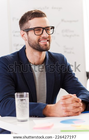 Confident business expert. Confident young man in smart casual wear looking away and smiling while sitting at his working place with whiteboard in the background - stock photo
